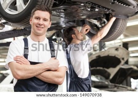 Mechanics At Work Shop. Confident Young Mechanic Standing With His Arms Crossed And Smiling At Camera While Another One Working On The Background