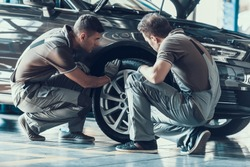 Mechanics Checking Wheel Bearings in Car Workshop. Two Professional Caucasian Adult Technician Master in Uniform in Front of Automobile in Garage. Repairing Car Service Concept