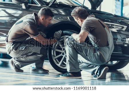 Mechanics Checking Wheel Bearings in Car Workshop. Two Professional Caucasian Adult Technician Master in Uniform in Front of Automobile in Garage. Repairing Car Service Concept #1169001118