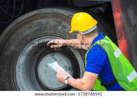 Mechanics checking wheel in cargo container. Professional technician pre-check forklift truck tires, safety concept. Imagine de stoc ©
