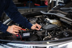 mechanics hand check electrical wiring vehicle system in a car service