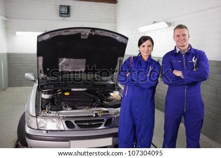 Mechanics next to a car a garage