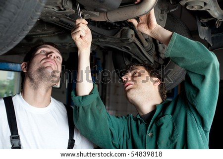 Mechanics repairing car in garage under the car.