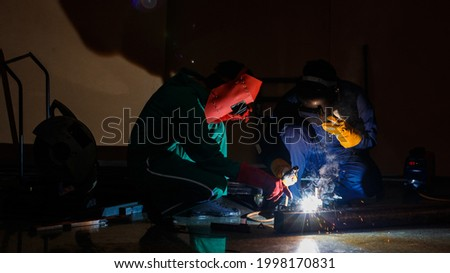 Mechanics workers work overtime hardly at night in a factory. Engineers wearing safety outfits with mechanic  jumpsuits, gloves, boots, and welding helmets working on metal welding. Foto stock ©