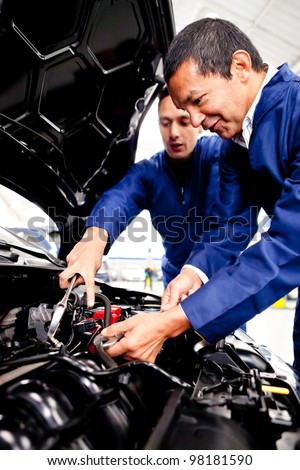 Mechanics working at the garage and fixing a car