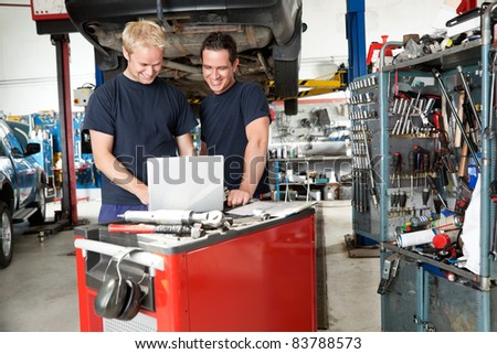 Mechanics working on laptop in auto repair shop