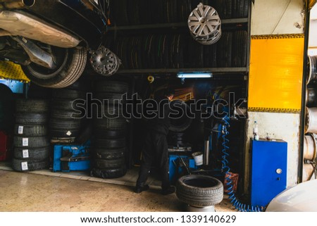 Mechanics working on tires in tire shop #1339140629