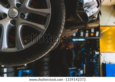 Mechanics working on tires in tire shop #1339142372