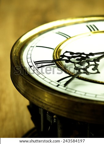 Mechanism of old clock on wooden background. Clock face and hands showing five minutes to midnight.