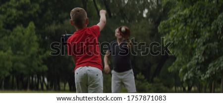 MED Father and son playing baseball catch in the park on a rainy day. Family time spent together. Shot with 2x Anamorphic lens Stock photo ©