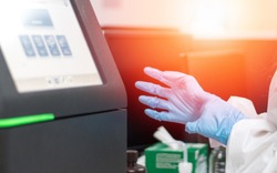 Med lab technologist using DNA sequencing equipment in science room. Chemist or scientist wearing blue medical glove working in hospital or university research laboratory.