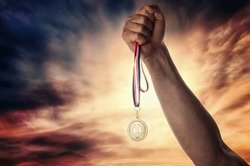 Medal for first place in the athlete's hand against a dramatic sky