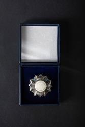 Medal, insignia, in an open box on black velvet, on a dark background