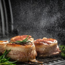 Medallions steaks from the beef tenderloin covered bacon on grill with smoke dark background.