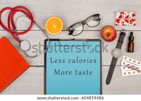 "Medecine concept - clipboard with text ""Less calories more taste"", book, pills, eyeglasses, watch, fruit and stethoscope on white wooden background"