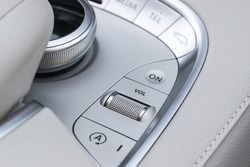 Media and navigation control buttons of a Modern car. Car interior details. White leather interior of the luxury modern car. Modern car interior