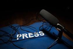 Media Journalism Global Daily News Content Concept. Blue journalist (press) vest in dark with backlight and fog. Media microphone on journalist vest. Selective focus