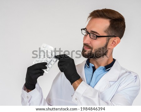 Medic in black medical gloves. Male doctor is holding medication. Concept doctor recommends taking pills. Portrait of doctor on light background. Blisters with pills in hands of virologist. Treatment Stok fotoğraf ©
