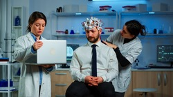 Medic in neuroscience working in neurological research laboratory developing brain experiment holding laptop explaning to man brainwave scanning headset side effects of nervous system treamtment.