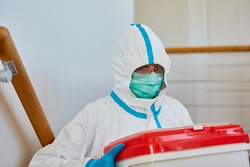 Medic in protective clothing during organ donation transport for surgery in clinic