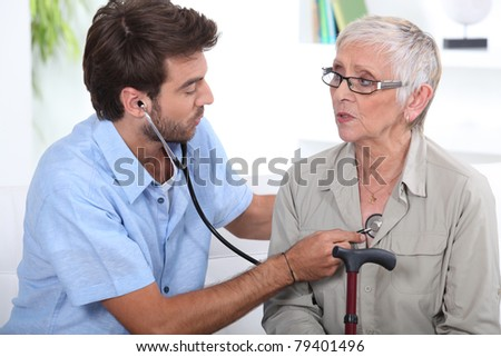 Medic listening to a senior woman's chest - stock photo