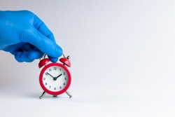 medic person holding alarm clock over grey background. copy space. studio shot. minimal. medicine time concept.