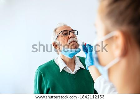 Medic taking sample for coronavirus testing. Coronavirus test. Medical worker in protective suite taking a swab for corona virus test, potentially infected senior man  Photo stock ©