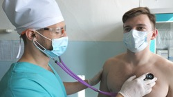 Medic with stethoscope listens lungs of patient looks for COVID-19 symptoms. Doctor with examining man with stethoscope to coronavirus pneumonia signs. Physician checking chest of guy at the hospital.