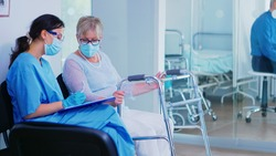 Medical assistant with face mask against coronavirus in hospital waiting room helping invalid senior woman with walking frame to fill documents. Patient entering in hospital corridor.