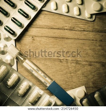 Medical background backdrop with frame border of pills tablets drugs and mercury thermometer on wooden table. Pharmacy.