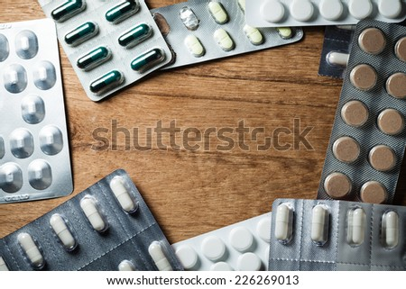 Medical background backdrop with frame border of pills tablets drugs on wooden table. Pharmacy.