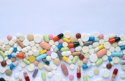 Medical background. Heap of medicine pills and capsules on a white background.