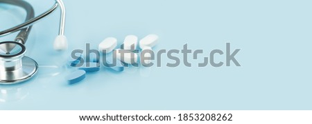 Medical background. white and blue capsule tablets or pills on the table with stethoscope. Close up. Healthcare pharmacy and medicine concept. Painkillers or prescription drugs consumption banner Сток-фото ©