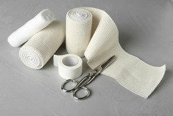 Medical bandage rolls, sticking plaster and scissors on grey table
