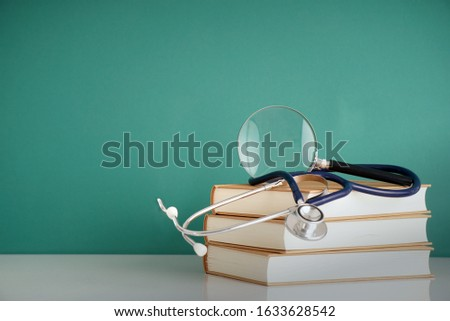 medical books, stethoscopes and magnifying glasses
