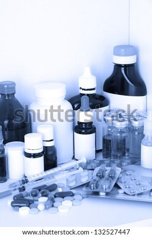 Medical bottles and pills in blue light