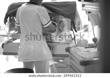 Medical checkup in neonatal intensive care unit; back of a doctor opening baby incubator