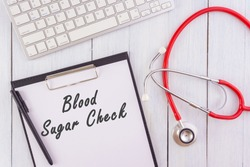 medical concept.BLOOD SUGAR CHECK written on notepad,stethoscope,keyboard on wooden table.white background.