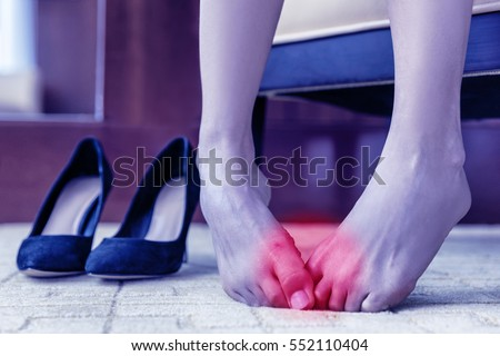 Medical concept. Foot pain. Body health problem, healthy feet swollen joints or blisters, wounds on skin. Painful barefoot woman at home or office with high heels in the background #552110404