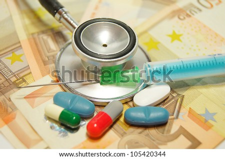 medical concept - health care costs - Stethoscope and syringe on money background and pills - stock photo
