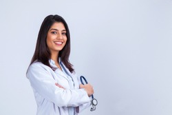 Medical concept of Indian beautiful female doctor in white coat with stethoscope, waist up. Medical student. Woman hospital worker looking at camera and smiling, studio, gray background