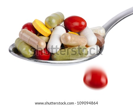 Medical concept: spoon piled with colorful pills, with one tablet falling down, isolated on white