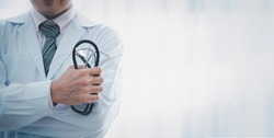 Medical concept standing with a stethoscope sideways Health care and medical with a stethoscope in hand Hospital examination room background