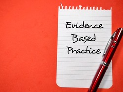 Medical concept.Text Evidence Based Practice writing on notepaper with pen on a red background.