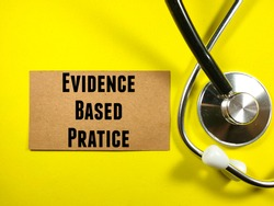 Medical concept. Text EVIDENCE BASED PRATICE on brown card with stethoscope on yellow background.