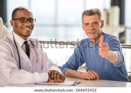 Medical concept. The doctor and patient smiling and thumbs up. Looking at camera.