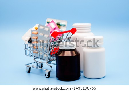 Medical concept. Various capsules, pack of medicines in shop trolley with medicine bottles on blue background. Pills concept. Buy and shopping medicine.