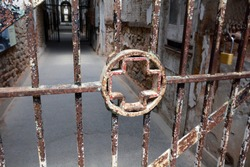 Medical Cross Symbol in the Bars of an Abandoned Prison Hospital Cell Block