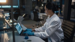 Medical Development Laboratory: Female Scientist Works on Laptop, Enters Data for Further Analysis. Pharmaceutical Lab for Medicine, Biotechnology, Bio Chemistry, Drugs, Vaccine Research. Evening Work