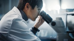Medical Development Laboratory: Portrait of East Asian Scientist Looking Under Microscope, Analyzes Petri Dish Sample. Pharmaceutical Lab doing Medicine, Biotechnology, Microbiology, Drugs Research.